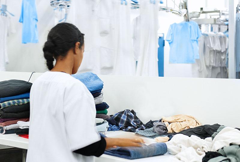 Die Wäscherei Bohnet faltet Wäsche maschinell und per Handarbeit