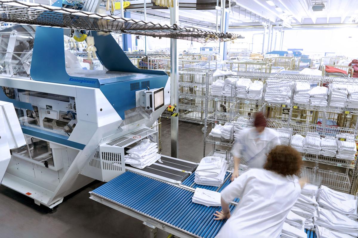 Mitarbeiter, die die automatisch zusammengelegte Wäsche aus der Faltmaschine in Empfang nehmen